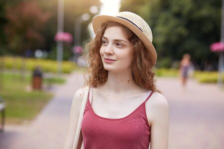 Outside image of beautiful tender model posing in green park, spending time at green space, being impressed by nature, looking aside, wearing straw hat and red top, standing in middle of local street. Reklamní fotografie