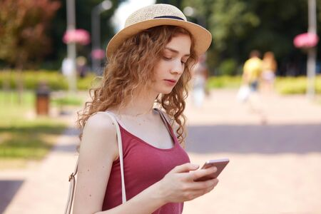 Outdoor shot of pensive cute young female holding her mobile phone in one hand, looking attentively at its screen, typing messages, checking social networking sites, spending her spare time.