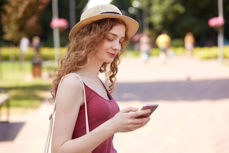 Portrait of good looking positive girl being in good mood typing messages to her friends having walk in recreation zone, holding smartphone in one hand. People and free time activities concept. Reklamní fotografie