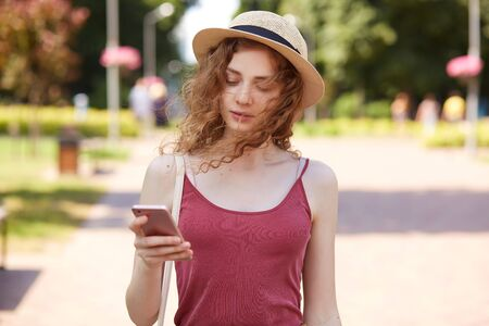 Tender sweet curly haired girl walking along green summer street, having smartphone in her hand, being focused on her mobile phone, making new post attentively, wearing casual clothes. Summer concept.