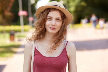 Image of beautiful positive young female looking directly at camera, standing in middle of park, smiling sincerely, having curly hair, spending her free time, wearing casual clothes, accessories.
