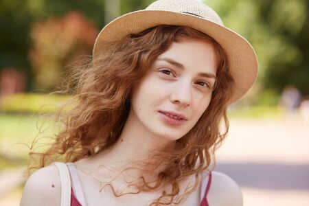Close up portrait of attractive young lady in straw hat. Foxy haired charming woman with brown eyes looking at camera with gentle, has calm facial expression, posing isolated over park background.