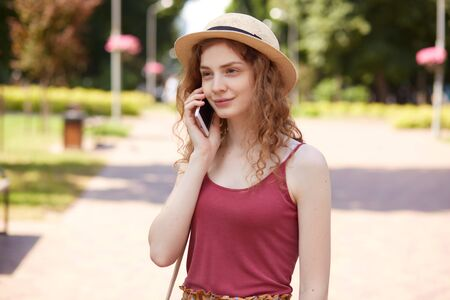 Horizontal shot of beautiful young woman in straw hat and burgundy t shirt, being in city park, having rest with friends, calling to her boyfriend via smartphone, has pleasant facial expression. Reklamní fotografie