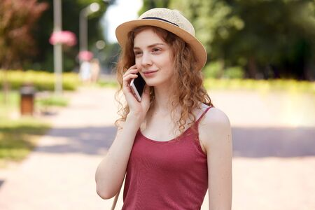 Image of cute tender girl having walk in park, enjoying her summer holidays, holding mobile phone near ear, listening carefully to speaker, wearing casual clothes, being satisfied with her rest.