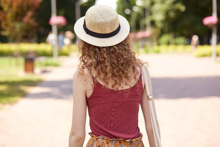 Back view of slender curly haired female wearing straw hat and red shirt, having bag on her shoulder, walking along paved street, spending time around nature in local park. Summer day concept.