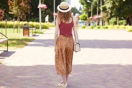 Full length photo from back view of young slender lady walking in tree shadow, fond of nature, spending lunchtime in recreation zone, wearing red shirt, orange skirt, sshoulder bag and straw hat.
