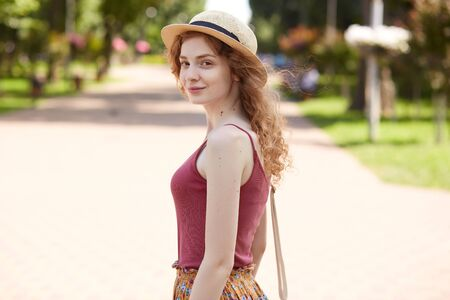 Portrait of smiling attractive girl having romantic look, enjoying time in local greenspace, looking directly at camera, having pleasant facial expression, being in good mood. Youth concept. Reklamní fotografie