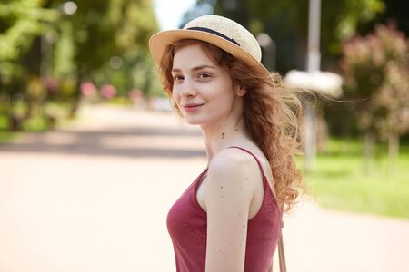 Image of adorable beautiful youngster looking aside, standing in middle of summer park, smiling sincerely, having pleasant look, wearing straw hat, red shirt, having bag on shoulder. Youth concept. Imagens