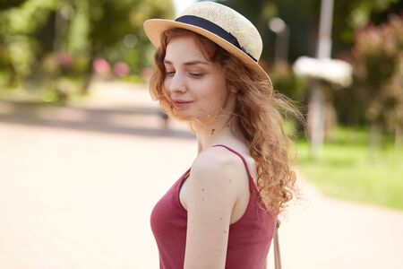 Outdoor shot of thoughtful attractive young lady with fair curly hair, posing in park, having summer holidays, looking aside, being in romantic mood, wearing casual items of clothes. Summer concept. Reklamní fotografie