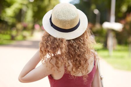 Back view of slender female with fair and curly hair wearing straw hat and red shirt, touching her hair with hand, having walk in park during lunch time, being fond of nature. Youth concept.