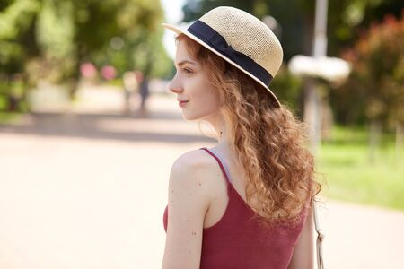 Profile of pensive beautiful active girl wearing straw summer hat and red shirt, having pleasant facial expression, looking straightforward, having curly fair hair, enjoying her weekends in park. Imagens