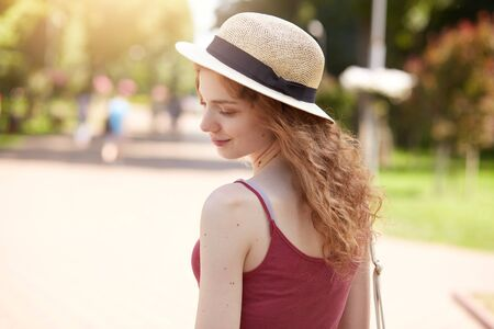 Horizontal shot of beautiful slim girl with wavy hair standing in park turning back to camera, wearing straw hat, burgundy casual t shirt, has rest with friends in open air, looks romantic and gentle. Фото со стока - 129221730