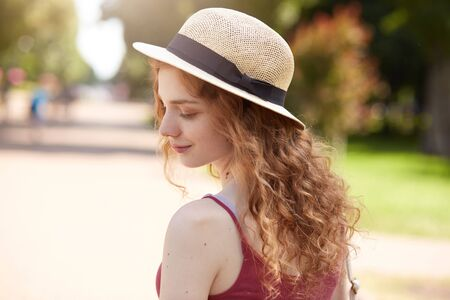 Outdoor shot of tender adorable youngster standing in park with almost closed eyes, being in good mood, inspired by summer weather, wearing straw hat and red shirt. Youth activities concept.