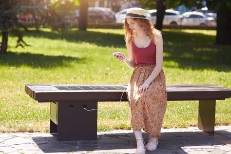 Image of young girl charges mobile phone via USB outdoors, female sitting on bench with solar panel in town park. Public charging, modern technology, alternative electricity, renewable energy concept.
