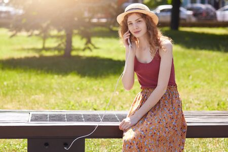 Outdoor shot of attractive woman charging her phone on free multipurpose solar panel incorporated in to sitting bench for citizens, wearing hat, t shirt and floor skirt, looking directly at camera.