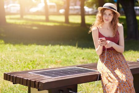 Outdoor photo of attractive woman with wavy hair, wearing hat, floor skirt and casual r shirt, sitting on bench in park, charging her device via alternative energy. Modern technology concept.