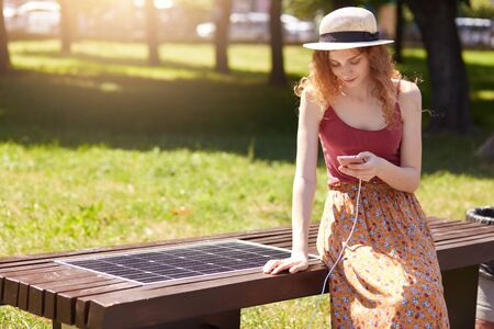 Outdoor short of attractive girl charges mobile phone via USB, charming female sitting on bench with solar panel in park. Modern technology, ecology, alternative energy, public charging concept. Stock Photo