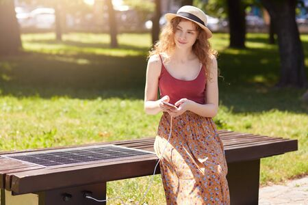 Alternative energy solutions in modern city. Young woman having rest in park, sitting on innovative bench and charging mobile device from built in USB port. Ecology, modern technology concept. Stock Photo
