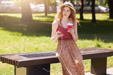 Horixontal shot of young woman charging mobile phone while sitting on bench with solar panel, female has stylish look, holding plastick cup of takeaway coffee, looking aside. Alternative energy.