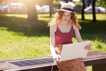 Photo of young foxy haired woman working with laptop in open air, charging her device on innovative bench built in USB port, charming female wearing hat, burgundy t shirt and skirt working online. Banque d'images