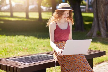 Photo of young woman working with laptop, charging her device on innovative bench built in USB port. Green energy solutions in modern smart city. Alternative energy, ecology and online work concept.