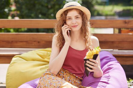 Image of young foxy haired woman in city garden or park, sitting on frameless chair and holding ice cream in hands, has conversation with boyfriend via smart phone, spending hot summer day outdoor.