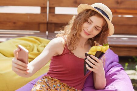 Close up portrait of smiling relaxed young girl taking selfie, holding smartphone in one hand, having food, sitting at colorful beanbags, posing over wooden fence outside. Rest time concept. Фото со стока