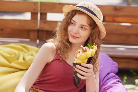 Delighted curly haired model lying on beanbags at cafeteria, looking aside, holding food in one hand, wearing straw hat and red top, being relaxed, chilling out. Free time activities concept.