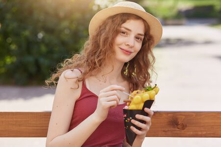 Attractive girl in casual clothes sits with ice cream at wooden bench and posing into camera. Young student female having rest after classes in beautiful park in summer, enjoys hot days with friends.