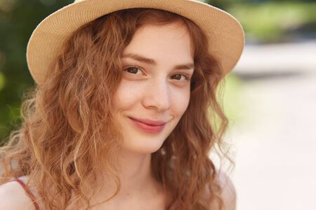 Close up outdoor portrait of young attractive girl wearing straw hat, has foxy wavy hair, looking directly at camera, has charming smile, posing in city park, looks calm and happy. People concept.
