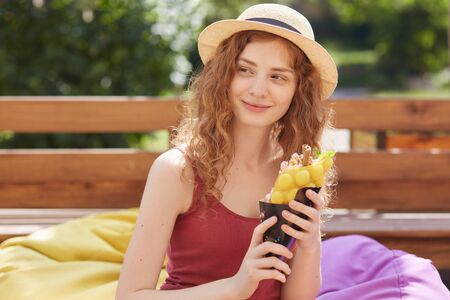 Summer and people concept. Young woman or teenage girl wearing casual clothes, holdinmg ice cream in hands, looking mysteriously aside, spending time with friends, posing over city park background.