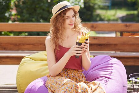 Outdoor shot of young female with foxy curly hair, sits on frameless chair smiling, looking aside and holding big ice cream in her hands, being in park in summer, cools with ice cream in hot weather.