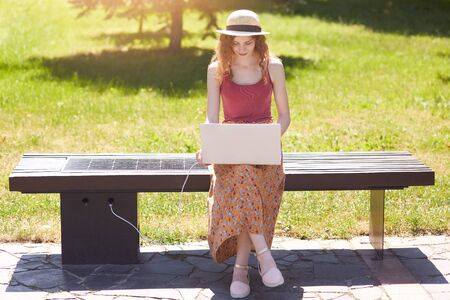 Slender attrective girl looking for information in net, laptop charging with help of solar panel built in wooden bench, using advantages of new technologies, being in good mood. Eco friendly concept.
