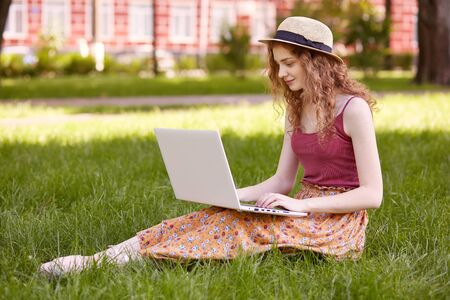 Portrait of young teenager sitting on green grass in park with portable computer on legs, spending summer day outdoor, using laptop and wireless Internet for writting course work. Student concept.
