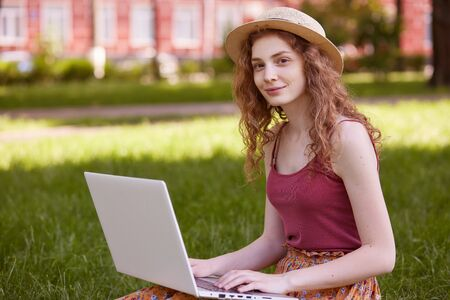 Horizontal shot of pretty young woman sitting on green grass in park with portable computer on legs during summer day, using wireless INternet for online working, female wearing t shirt and straw hat.