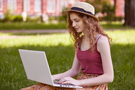 Portrait of pretty young woman sitting on green grass in park with laptop on legs, spending summer day working outdoor, using laptop and wireless Internet for online work. Lifestyle concept.
