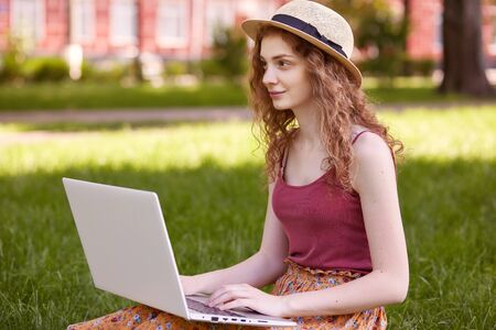 Outdoor shot of pretty young woman sitting in park with laptop on legs, spending summer day working outdoor, looking at distance, wearing t shirt, skirt and hat, girl likes online work in open air.