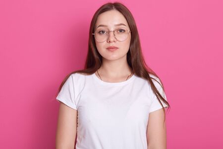 Close up portrait of beautiful young woman wearing spectacles and white casual outfit, feels happy, looks at camera, model posing isolated over pink studio wall, has long hair. People concept.