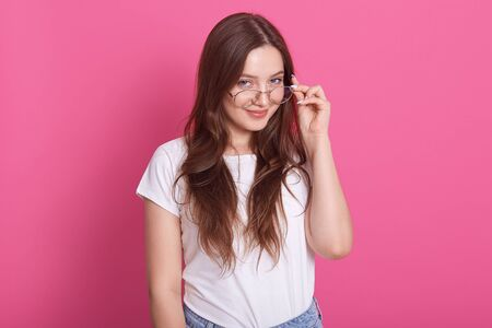 Indoor shot of attractive young woman with long hair keeps hand on rim of spectacles, wearing casual outfit, model posing against pink studio wall, looks smiling directly at camera. People concept. 스톡 콘텐츠
