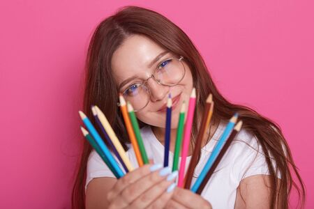 Indoor shot of young beautiful girl artist wearing white casual shirt and eyewear, model posing with colored pencils in her hands, charming female looks at camera, showig her pencils. Drowing concept. Фото со стока - 129221633