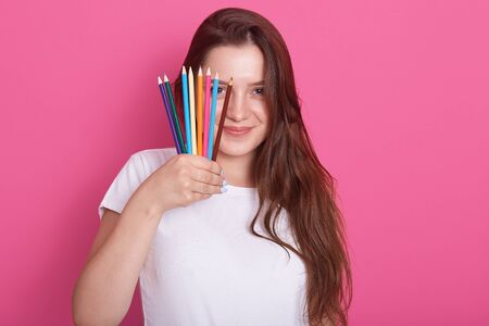 Close up portrait of girl artist in white casual shirt, covering half of her face with colored pencils which holding in her hand, has long hair, posing isolated over rosy background, looks at camera.