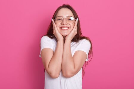 Image of happy young woman filled with hope and positive attitude looking at camera with joyful smile and keeps hands on cheeks, posing over pink studio background, dressed casual outfit and glasses.