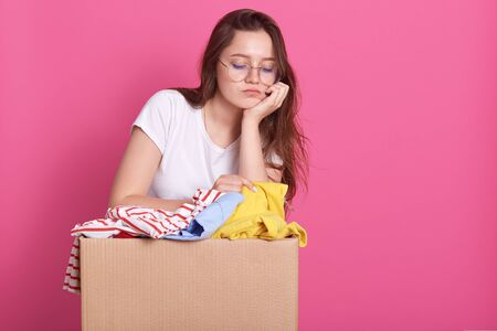 Close up portrait of unhappy young woman posing with box of clothes donation, has sad facial expression, looking down, keeps hand under chin, packing clolothes for secondary use for poor people.