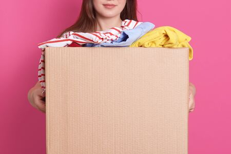 Indoor portrait of faceless girl standing with cardboard box in hands, holding carton box full of fashionable clothes isolated on rosy background. Donation, charity and volunteering concept.