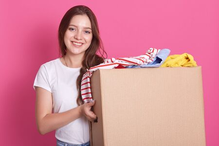 Horizontal shot of female stands smiling near both with reusable clothing for poor peoplw isolated over pink background in studio, attractive woman making charity, posing with happy expression.