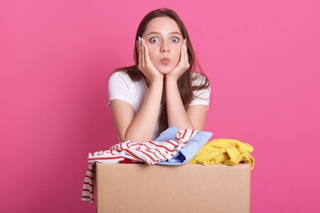 Studio shot of cheerful volunteer standing isolated over pink background in studio, near box with donated clothes, young attractive woman makes air kiss, looks directly at camera. Charity concept.