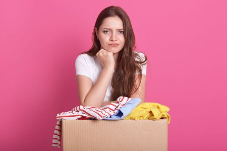 Close up portrait of beautiful woman with pensive facial expression, posing near box with old clothes, decides whom to give things for secondary use, standing over pink background. Donation concept. Фото со стока