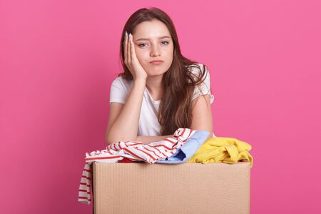Close up portrait of happy young woman with clothes donation standing over rose background, packing reusable clothes for poor people, attractive female keeps hand under chin, looking bored at camera.