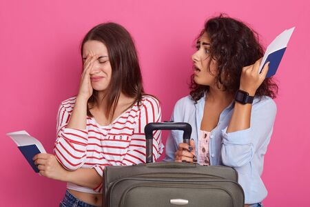 Close up portrait of woman being late for plane or confuses date of flight, sit near their suitcase, holds tickets and pasports in their hands, one girl crying and other lady blaming her for mistake.