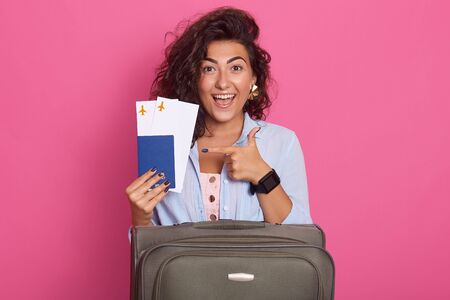 Studio shot of woman with suitcase, showing her tickets for plane in her hands with fore finger, isolated over rosy background, model with toothy smile, experesses happyness, wearinf stylish outfit. Banco de Imagens